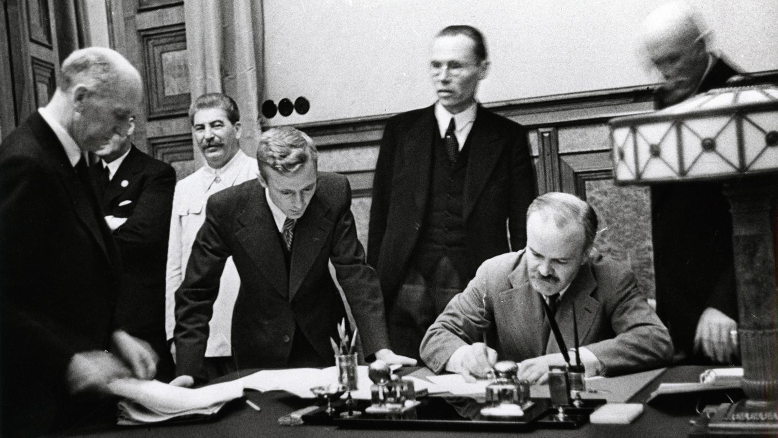 1939 Год. Председатель СНК СССР и нарком иностранных дел СССР В.М.Молотов подписывает советско-германский договор о ненападении 1939 года. Присутствует И.В.Сталин. Фото: архив